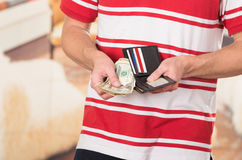 Man wearing red white striped shirt holding wallet Stock Photo