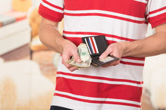 Man wearing red white striped shirt holding wallet Stock Photos