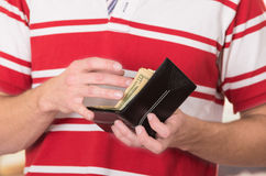 Man wearing red white striped shirt holding wallet Royalty Free Stock Photos