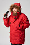 Man wearing red winter Alaska jacket  with fur hood on Stock Photo