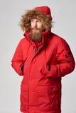 Man wearing red winter Alaska jacket  with fur hood on. Portrait of a man wearing red winter Alaska jacket  with fur hood on,  looking forward out of frame Stock Image