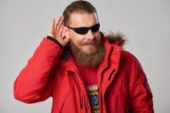 Man wearing red winter Alaska jacket  with fur hood on. Portrait of a man wearing red winter Alaska jacket  with fur hood on,  looking forward out of frame Stock Photo