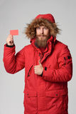Man wearing red winter Alaska jacket with fur hood on. Portrait of a man wearing red winter jacket with hood on showing blank credit card and gesturing thumb up Royalty Free Stock Image