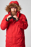 Man wearing red winter jacket with binoculars. Portrait of a man wearing red winter jacket with fur hood on with binoculars, studio shot Stock Images