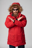 Man wearing red winter jacket gesturing stop enough hand sign. Portrait of a serious bearded man wearing red winter jacket and sunglasses with hood on, gesturing Royalty Free Stock Images