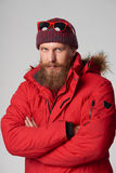 Man wearing red winter jacket. Portrait of a serious man wearing red winter jacket with mustache and beard with intense look Royalty Free Stock Images