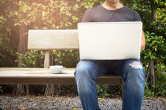 Man wearing ripped jean with cup of coffee working on laptop. In the garden Stock Photography