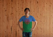 Man wearing Romani people flag color shirt and standing with akimbo on the wooden wall background. Blue and green background. Representing the heavens and royalty free stock photo