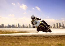 Man wearing safety suit riding sport racing motorcycle on sharp curve highway royalty free stock image