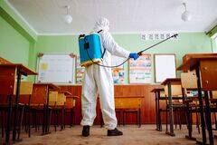 A man wearing a sanitizing equipment and protective suit disinfects the classroom to prevent coronavirus spread among students and