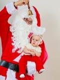 Man wearing santa claus costume holding baby Stock Images