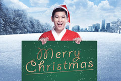 Man wearing santa claus costume holding banner with merry christmas writing Stock Images