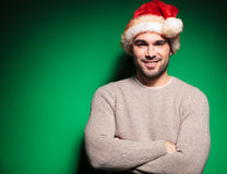 Man wearing santa claus hat standing with hands crossed. Relaxed young man wearing santa claus hat standing with hands crossed on green background Royalty Free Stock Photography