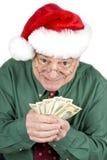 Man Wearing Santa Hat Holding American Money. A mature man in Santa hat holding a bunch of American dollars Stock Image