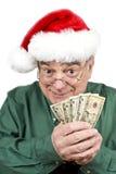 Man Wearing Santa Hat Holding American Money. A mature man in Santa hat holding a bunch of American dollars Royalty Free Stock Photography