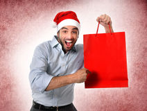 Man wearing santa hat holding Christmas shopping bag smiling happy. Happy man in Santa hat holding and pointing red shopping bag in Christmas consumerism , sale Stock Photography