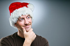 Man Wearing Santa Hat Thinking Of What Gifts To Give Royalty Free Stock Images