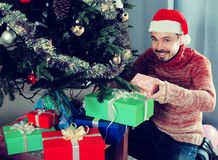 Man wearing Santa puts gifts under the Christmas tree Royalty Free Stock Photos