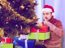 Man wearing Santa puts gifts under the Christmas tree Royalty Free Stock Image