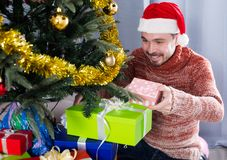 Man wearing Santa puts gifts under the Christmas tree Royalty Free Stock Photo