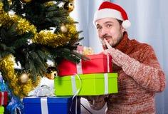 Man wearing Santa puts gifts under the Christmas tree Stock Photo
