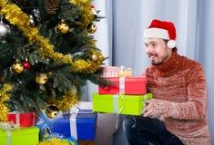 Man wearing Santa puts gifts under the Christmas tree Stock Photos