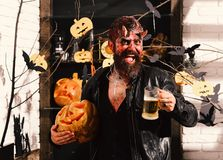 Man wearing scary makeup holds mug of beer. With Halloween decor on background. Demon with horns and cheerful face holds jack o lantern. Devil or monster royalty free stock photos