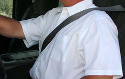 Man wearing seatbelt. Man in white shirt in an auto with seatbelt on stock photography
