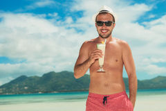 Man wearing shades and drinking a cocktail on the beach. Smiling young man wearing shades and drinking a cocktail on the beach while having his hand in pocket Royalty Free Stock Images