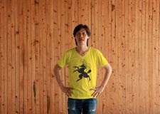 Man wearing Shaffhausen flag color shirt and standing with akimbo on the wooden wall background. The canton of Switzerland Confederation royalty free stock image