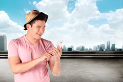 Man wearing shirt and hat using his cellphone Royalty Free Stock Photography