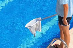 Man wearing shorts cleans the swimming pool with a net Royalty Free Stock Photography