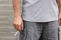 Man wearing shorts holds cigarette by his side. A man wearing shorts with pockets holds a cigarette by his thigh in the summertime Royalty Free Stock Image