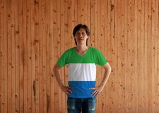 Man wearing Sierra leone flag color shirt and standing with akimbo on the wooden wall background. A horizontal tricolor of light green white and light blue stock photos