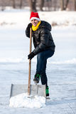 Man wearing skates working with snow shovel. Stock Photo