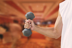 Man wearing sleeveless white shirt holding old dumbbell on blurred fitness club in hotel Stock Photos
