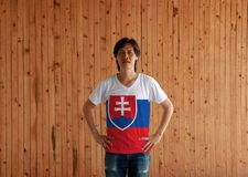 Man wearing Slovakia flag color shirt and standing with akimbo on the wooden wall background. White blue and red; charged with a shield containing a white royalty free stock photo
