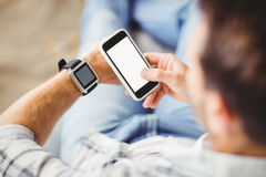 Man wearing smart watch and using mobile phone Royalty Free Stock Images