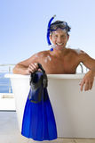 Man wearing snorkle and holding flippers whilst in bubble bath, smiling, portrait Stock Photography