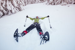 Man wearing snowshoes, lies in the snow Royalty Free Stock Photography
