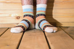 Man wearing socks with ornament. Men feet on the wooden floor royalty free stock image
