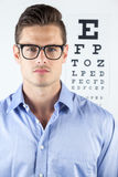 Man wearing spectacles with eye chart in background Stock Images
