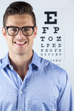 Man wearing spectacles with eye chart in background Royalty Free Stock Image