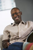 Man wearing spectacles and short-sleeved shirt, relaxing in chair at home, smiling, portrait (tilt) Stock Photos