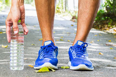 Man wearing sport shoes and picking up water bottle on running track in park Royalty Free Stock Photo