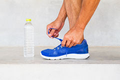 Man wearing sport shoes and picking up water bottle on running track in park Royalty Free Stock Photography