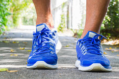 Man wearing sport shoes walking in the park Royalty Free Stock Images