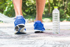 Man wearing sport shoes walking in the park with drinking water. Bottle on the ground, sport concept Stock Photography