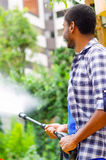 Man wearing square pattern blue and white shirt holding high pressure water gun, pointing liquid to green garden Royalty Free Stock Images