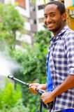 Man wearing square pattern blue and white shirt holding high pressure water gun, pointing liquid to green garden Stock Photography